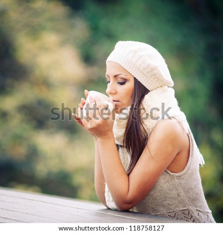 Young woman drinking from a cup outdoors in the nature.