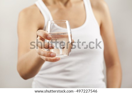 Young woman drinking  glass of water - Shutterstock ID 497227546