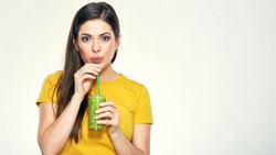 Young woman drinking green juice with straw. Isolated studio portrait on white.