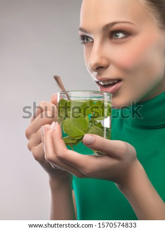Young woman drinking herbal tea, studio shot