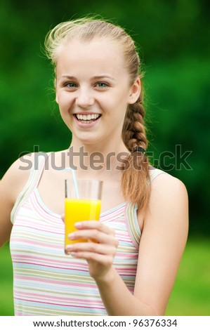 Young woman drinking orange juice after outdoor fitness exercise
