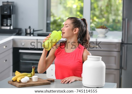 Young woman drinking protein shake in kitchen