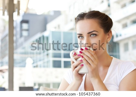 Young woman drinking tea in a cafe outdoors