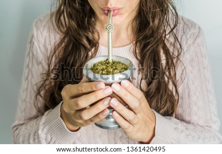 Young woman drinking traditional Argentinian yerba mate tea from a calabash gourd with bombilla stick  Foto stock ©