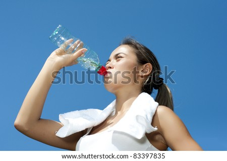 Young woman drinking water after exercise, summer park background