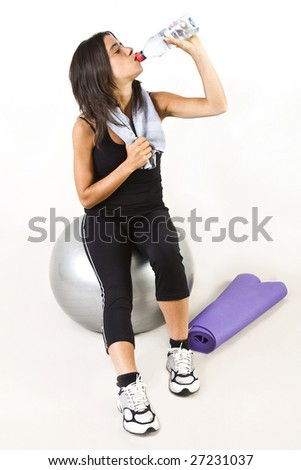 Young woman drinking water after gym on white background.