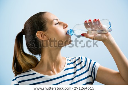 Young woman drinking water after jogging