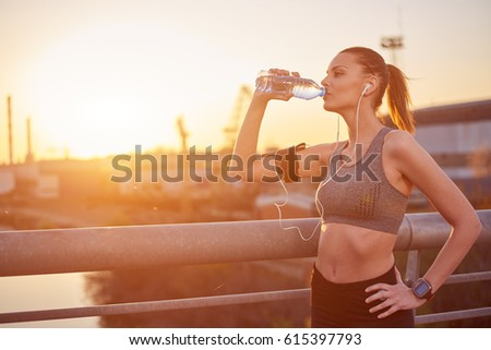 Young woman drinking water after running #615397793