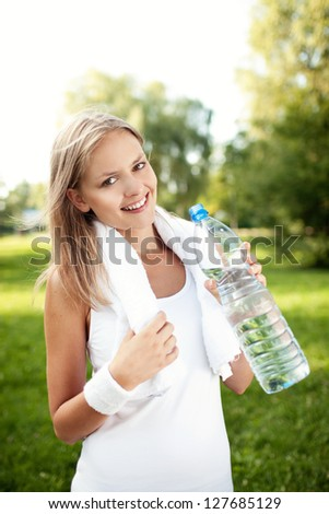 Young woman drinking water after training