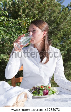 Young woman drinking water and eating a healthy salad outdoors on a restaurant patio