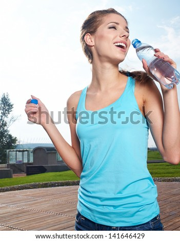 Young woman drinking water at outdoors workout #141646429