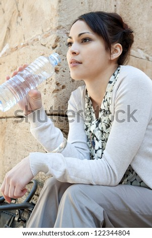 Young woman drinking water from a plastic blue bottle while sitting down near an old stone wall, outdoors.
