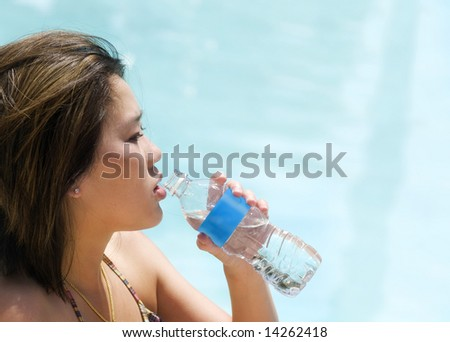 Young woman drinking water from clear plastic bottle with blank blue label.