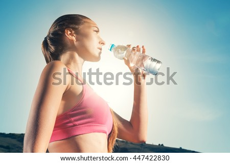 Young woman drinking water from plastic bottles after jogging. Girl quenches thirst after fitness outdoors. Lose weight. Healthy lifestyle.