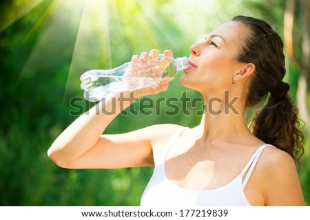 Young Woman Drinking Water from the bottle Healthy and Sporty Girl Doing Sport Outdoor Workout