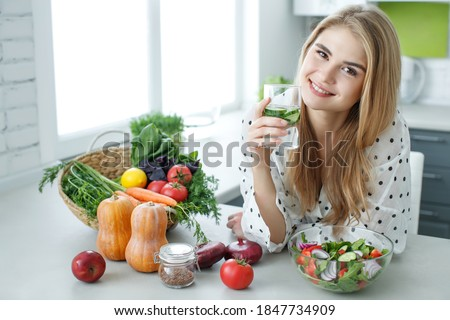 Young woman drinking water near the table with fruits and vegetables in the kitchen. Healthy food, drinks, diet, detox and people concept. High quality photo.