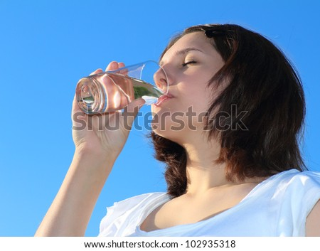 Young woman drinking water on sky background