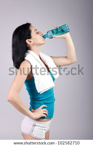Young woman drinking water with eyes closed.Brown background.