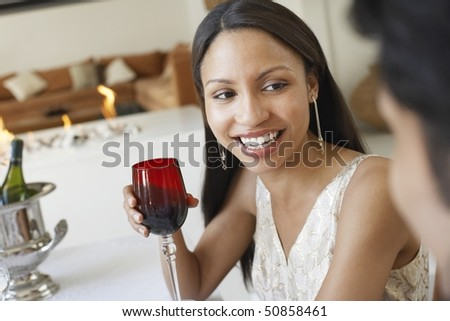 Young Woman Drinking Wine, socialising at formal dinner party