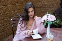 Young woman drinks coffee on the terrace of a street cafe. The woman is wearing a warm pink cardigan.