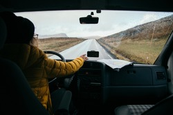 Young woman drive big old converted camper van, navigate smartphone on dashboard to use gps app on screen to arrive to camping ground destination. Road trip vanlife concept