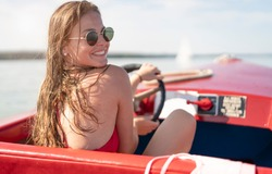 young woman drives a rental boat over the Chiemsee on a beautiful sunny day and sunbathes