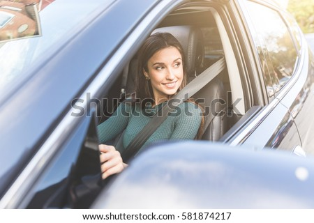 young woman driving a car in...