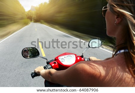 Young woman driving a motorbike on an asphalt road