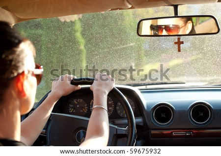 Young woman driving an old car. Selective focus on her hands and rear-view mirror.