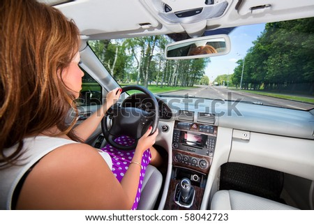Young woman driving car. Wide angle interior view.