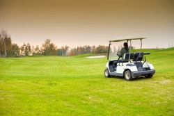 Young woman driving golf cart car on course to green