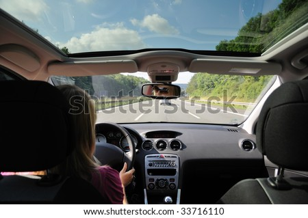 Young woman driving with her car