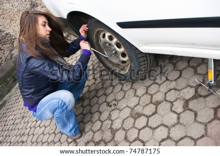 Young woman during the wheel changing