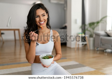 Young woman eating a healthy salad after workout. Fitness and healthy lifestyle concept.