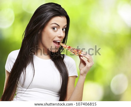 young woman eating a piece of pizza against a nature background