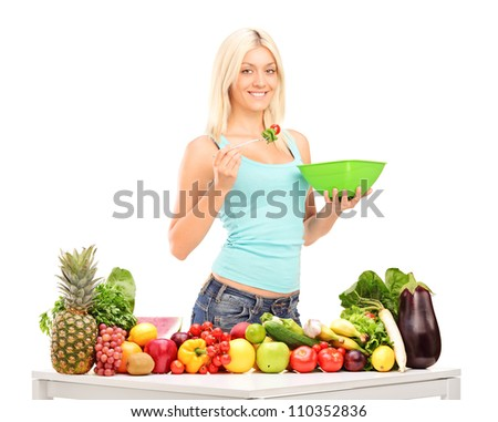 Young woman eating a salad, standing behind table full of fruits and vegetables