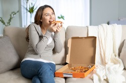 Young woman eating a slice of pizza at home. Attractive young woman eating tasty pizza in living room.