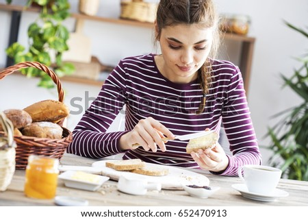 Shutterstock Young woman eating bread with butter