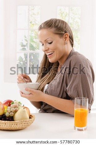 Young woman eating breakfast cereal and drinking orange juice, smiling.