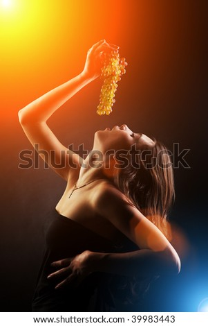 Young woman eating bunch of grapes. Dramatic light.