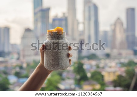 Young woman eating chia pudding on her balcony overlooking the big city.