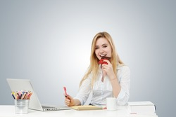 Young woman eating chocolate at the office