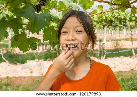 Young woman eating grape in the vineyard.