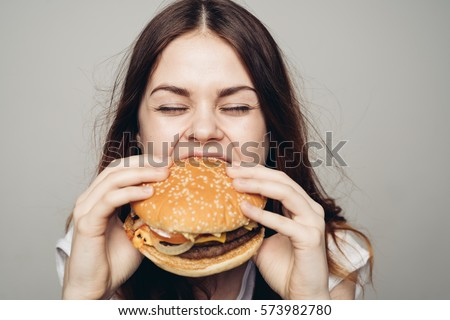 Young woman eating hamburger woman eating junk food, fatty food hamburger.