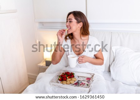 Young woman eating healthy breakfast in bed. Young woman eating breakfast in bed drinking coffee. Beautiful young woman smiling and eating strawberries .
