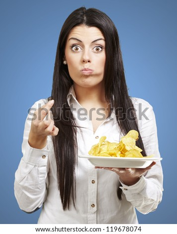 young woman eating potato chips against a blue background