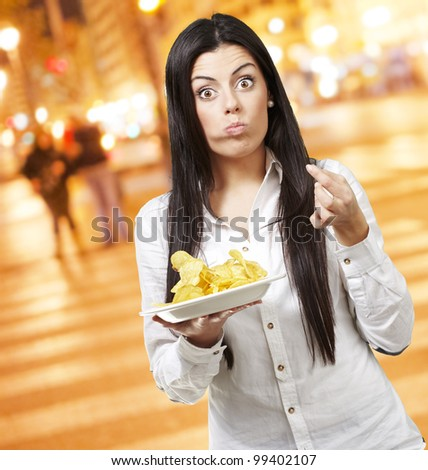 young woman eating potato chips against a city night background