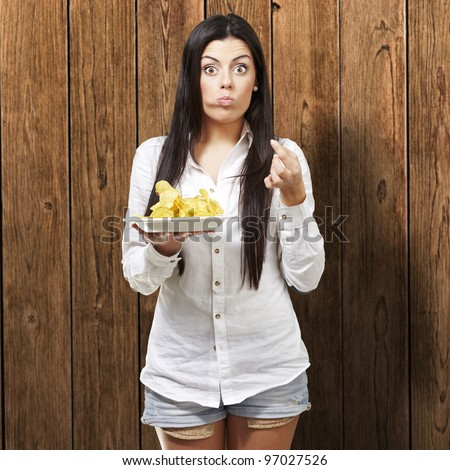 young woman eating potato chips against a wooden background - stock photo