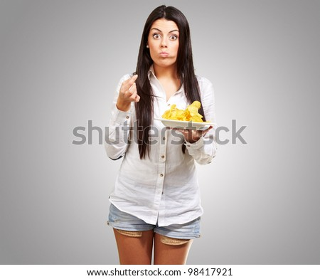 young woman eating potatoe chips against a grey background