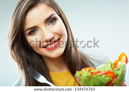 Young woman eating salad isolated portrait.